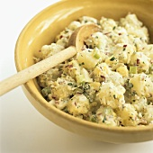 A Bowl of Potato Salad with a Wooden Spoon