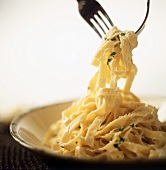 Fettuccine Alfredo Being Lifted From a Bowl by Two Forks