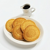 Five Pancakes on a White Plate with a Pitcher of Maple Syrup