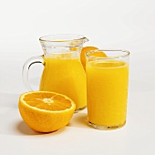 An Orange Half with a Pitcher and a Glass of Orange Juice