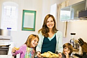A Woman and Two Children Smiling and Holding a Plate of Cookies