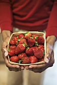 Hands Holding a Container of Strawberries