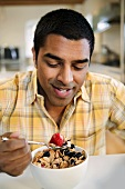 A Man Eating a Bowl of Bran Flake Cereal with Fresh Berries