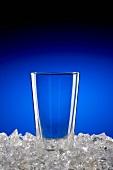 Leeres Glas auf zerstossenem Eis vor blauem Hintergrund