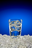 A Glass of Ice Water on Ice with Blue Background