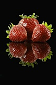 Three Ripe Strawberries on Black with Reflection