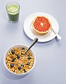 A Bowl of Oat Cereal with Blueberries, a Grapefruit Half and a Spirulina Fruit Smoothie