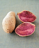 A Whole and a Halved Purple Sweet Potato on Woven Green Fabric