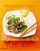 Thai Beef Salad on a Square Plate with Chopsticks and Water with Lime