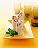 Red Pepper and Goat Cheese Tortilla Wraps on a Yellow Platter with Fresh Mint