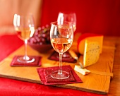 Glasses of White Wine on Red Coasters with Cheese and Grapes