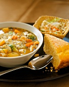 A Bowl of Hearty Root Vegetable Soup with Cornbread