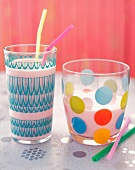 Two Colorful Glasses of Milk with Straws, One Full and One Half Full