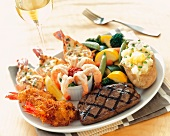 A Surf and Turf Platter with Grilled Steak, Three Types of Shrimp, Mixed Vegetables and Baked Potato