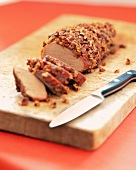 Pecan Encrusted Pork Loin with Knife on a Wooden Board