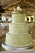 A Three Tier Wedding Cake with Green Fondant in a Reception Hall