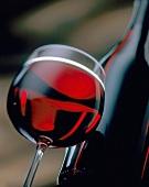 Rotweinglas vor Rotweinflasche