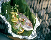 Whole Fish in a Banana Leaf with Scallions and Lemon on a Charcoal Barbecue