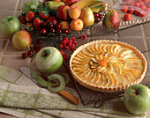 A Whole Apple Tart Surrounded by Fresh Fruit