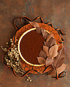 A chocolate caramel tart with chocolate leaves
