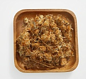 Dried arnica flowers in wooden dish