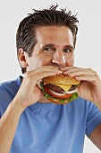 Man biting into succulent cheeseburger