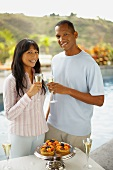 Couple with glasses of sparkling wine by swimming pool