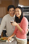 Young couple drinking red wine with meal in kitchen