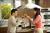 Young couple clinking glasses of red wine in kitchen