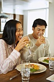 Young couple drinking white wine with lunch in kitchen
