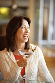 Laughing woman holding glass of Martini