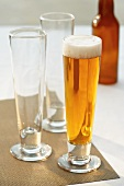A Glass of Lager with Two Empty Glasses