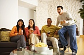 Friends watching television with beer, wine and crisps