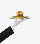A Gloved Hand Holding a Silver Tray with a Cheeseburger