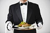 Butler serviert Hähnchensalat auf Silbertablett
