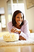 Woman lying on rug eating popcorn