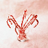 Candy Canes in a Glass on a Pink Background
