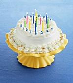 A Birthday Cake on an Yellow Stand with Lit Candles