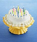 Geburtstagstorte mit brennenden Kerzen auf Kuchenständer