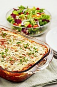 Lasagna in a Glass Baking Dish and Salad in a Serving Bowl