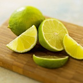 Whole and Sliced Limes on a Wooden Board, Close Up