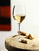 A Glass of White Wine with Corks and Corkscrew