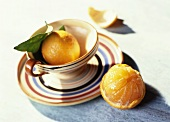 An Orange in and Next to a Striped Cup and Saucer