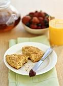 Scone, Erdbeermarmelade auf Messer, Beeren, Tee, Orangensaft