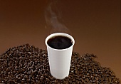 A Steaming Cup of Black Coffee on a Pile of Coffee Beans