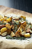 Roast potatoes with rosemary on baking parchment