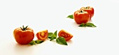 Whole and Sliced Tomatoes with Fresh Basil Leaves on a White Background