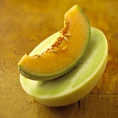 A Wedge of Cantaloupe on top of a Halved Honeydew Melon