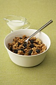 A Bowl of Granola with Raisins, Spoon and a Pitcher of Milk