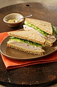 A Turkey Sandwich on Whole Wheat Bread with Romaine, Cheese and Dijon